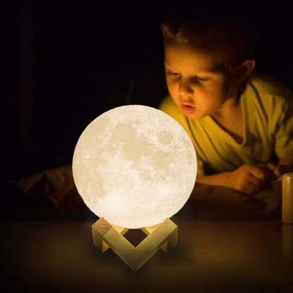 Boy playing with our moon lamp light, 3D printed. Children love to explore the universe and the Moon with our home decor light.