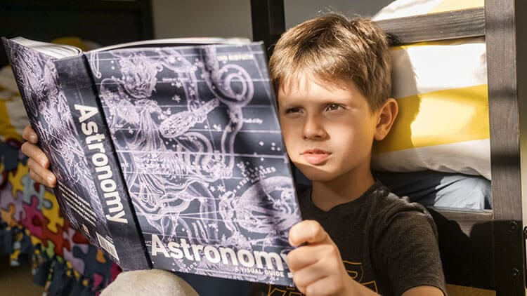 child reading a book about astronomy