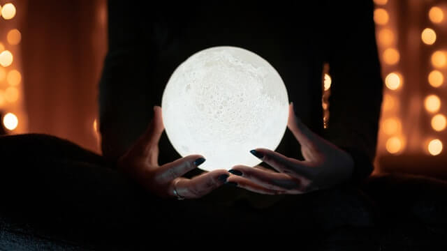 Woman holding the moon in her hands